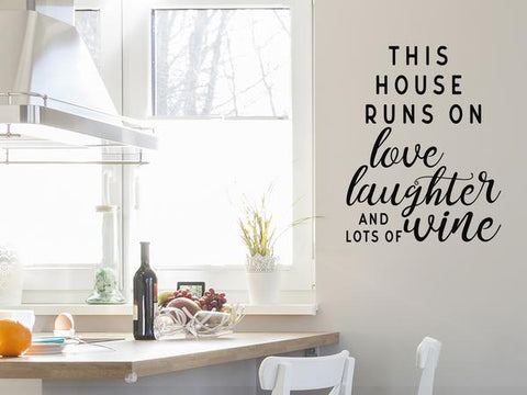 Wall decals for kitchen that say 'This house runs on love, laughter and a whole lot of wine' on a kitchen wall.