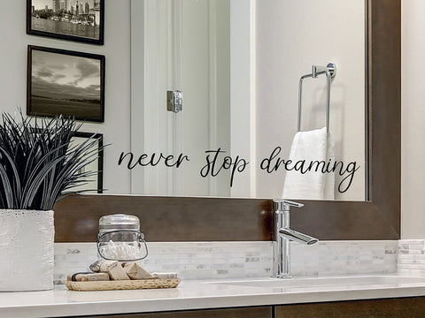 Wall decals for the bathroom that say, 'never stop dreaming' on a bathroom mirror.