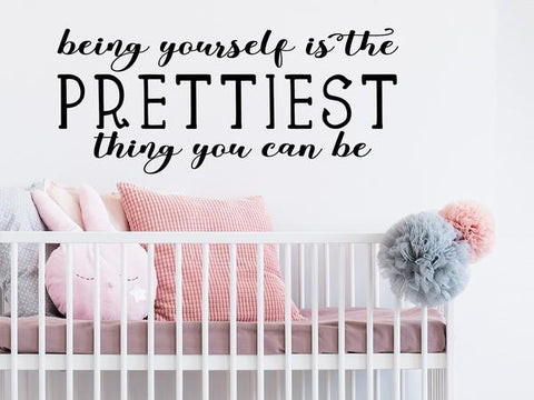 Wall decal for kids that says 'being yourself is the prettiest thing you can be' on a kid's room wall.