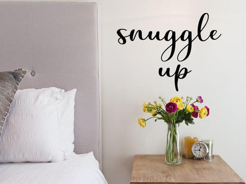 Wall decal for bedroom that says 'snuggle up' on a bedroom wall.