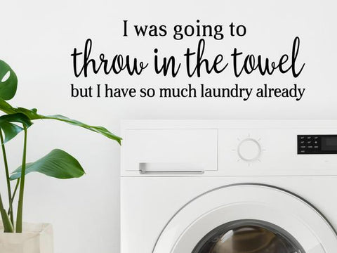 Laundry room wall decal that says, 'I was going to throw in the towel but I have so much laundry already' on a laundry room wall.