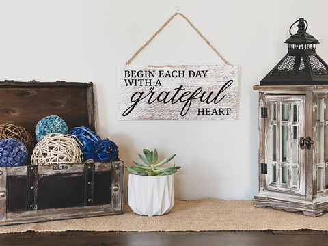Custom home wood sign that says, 'begin each day with a grateful heart' on a wall.