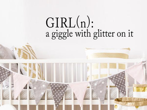 Wall decal for kids that says 'girl: a giggle with glitter on it' on a kid's room wall.