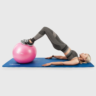Girl Exercising on a Proworks Yoga Mat with a Proworks Exercise Ball