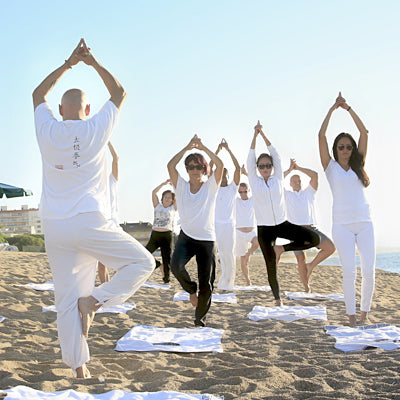 A Group of Women Performing Yoga on a Beach While on a Hen Party