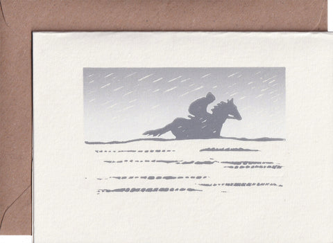 Racehorse greeting card. Hand printed linocut of a horse and jockey cantering on a snowy, winter day. Grey and light blue ink.