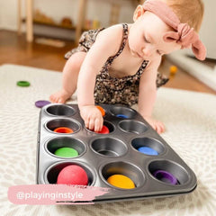 Baby playing with Grapat pieces in a muffin tray.