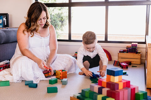 Mother and son practicing parallel play with magnetic tiles and blocks.