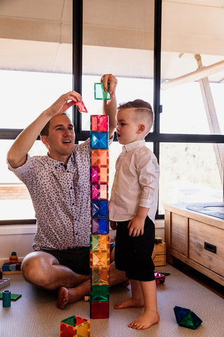 Father and son playing with magnetic tiles.