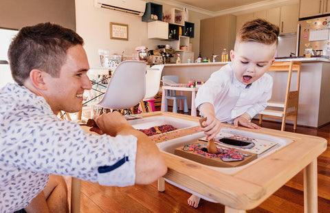 Father and son playing with rainbow sensory rice.