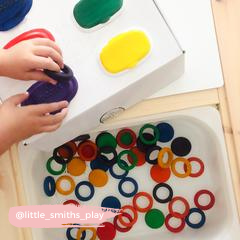 DIY activity using wooden toy coins and disposable wipe lids.