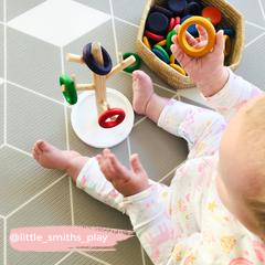 Baby playing with mug tree and wooden Grapat coins