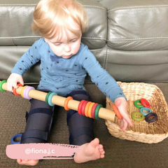 Toddler playing with a cardboard tube and Grapat rings.