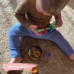 Toddler threading wooden rings onto a toy spatula.