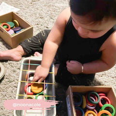 Baby playing with Grapat coins in a tray with rubber bands.