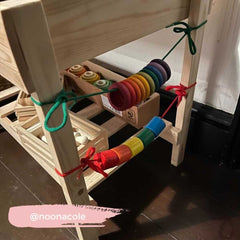 Wooden rings, looped onto a string and attached to a table.