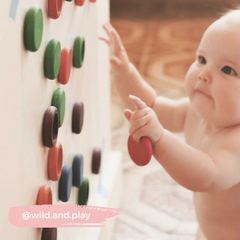 Baby playing with wooden toy coins on sticky wall