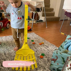 Little kid sweeping rings and coins to practice montessori-style practical skills