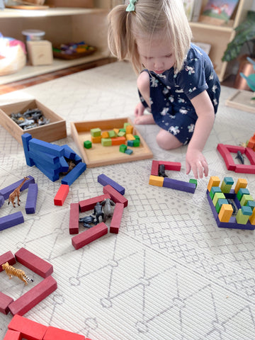 Little girl playing with wooden blocks making a zoo with animal figurines.