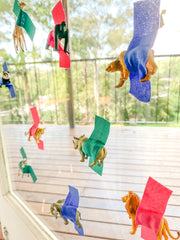 Small animal figurines taped to a window for a baby's activity.
