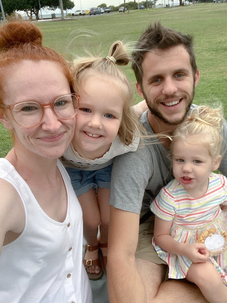 Family of four all smiling in a park.