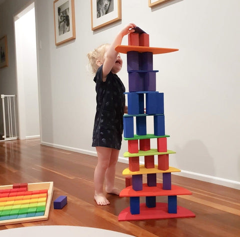 Young girl building a large block tower with quality wooden block tower.
