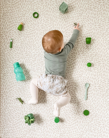 Baby playing on the floor with green open-ended toys