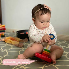 Baby playing stacking game with wooden rings.