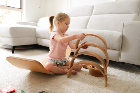 A little girl playing with a Grimm's wooden rainbow. Stacking it while sitting on a balance board.