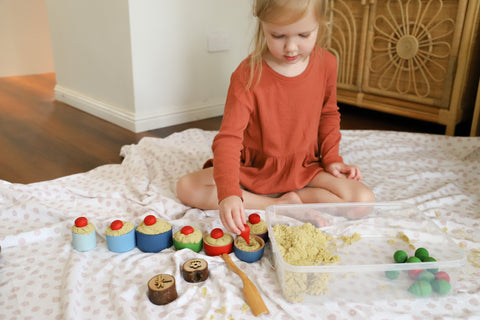 Little girl doing sensory play with kinetic sand and wooden bowls