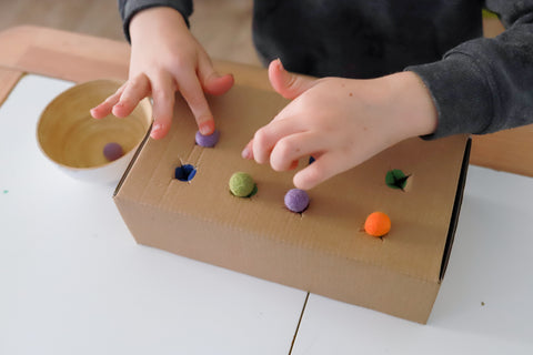 DIY recyclced play idea with pompom pushing for fine motor skills