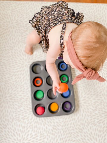 A baby playing with wooden toys in a muffin tray.