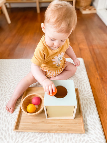 Child playing with an object sensory box and wooden balls from Grimm's toys.