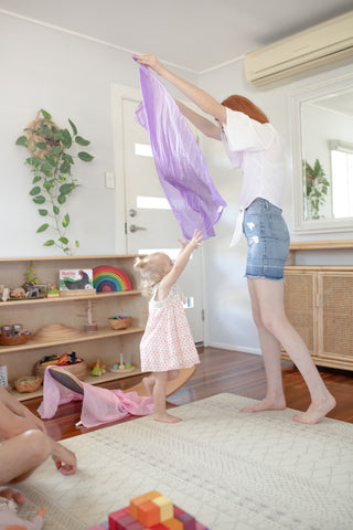 Mother and daughter playing with Sarah's Silks on balance board.
