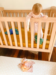 Baby playing with Sarah's Silk in their cot.