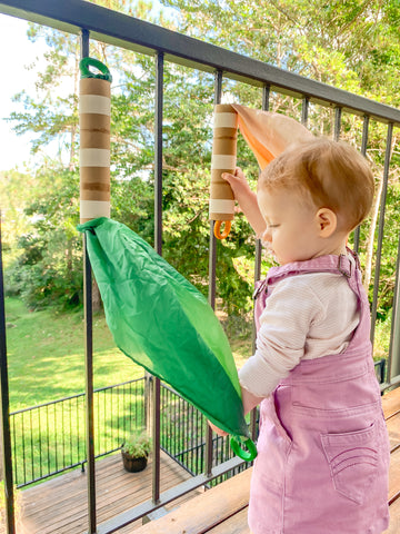 Invitation to play outside using sarah's silks and recycled cadrboard tubes.