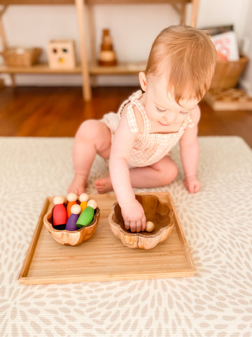A simple invitation to play for a baby with wooden peg dolls and bowls.