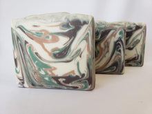 Load image into Gallery viewer, Cedar and Amber Handmade Soap -  This is a fresh scent rich with pine notes blended with warm cinnamon and clove.  A hearty base of cedarwood is mellowed with a gentle amber scent.  Ingredients:  Olive oil, coconut oil, organic palm oil, water, sodium hydroxide, shea butter, sweet almond oil, meadowfoam oil, caster oil, fragrance, kaolin clay, skin-safe colorants