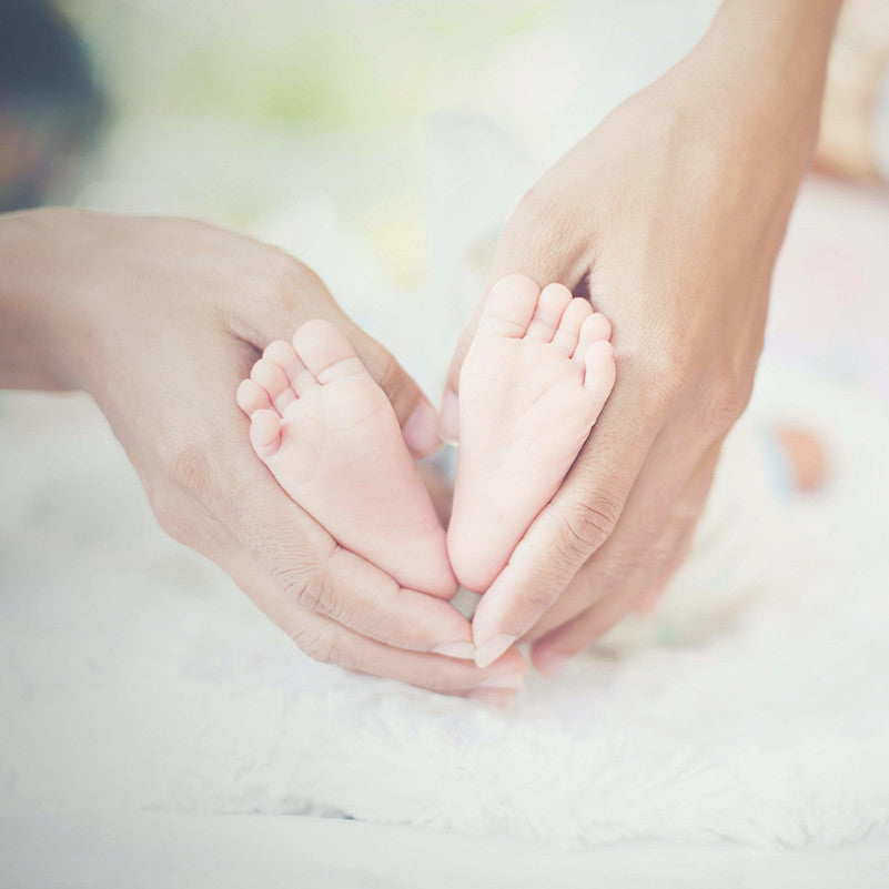 mother holding baby feet