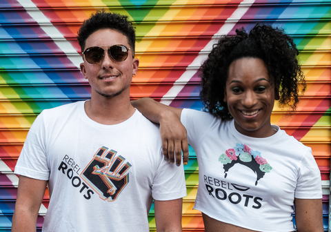 [ID: the founders of gc2b and the martha p. johnson institute have their arms around one another. he is wearing a rebel roots T shirt, and she is wearing an MPJI crop top. end ID]