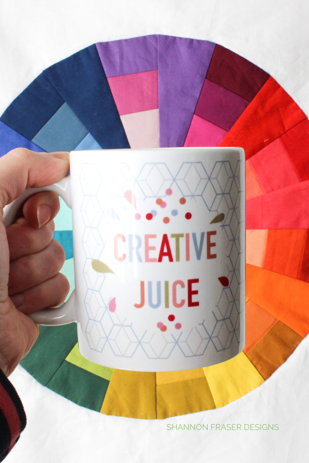 """my hand holding my """"creative juice"""" mug with my colour theory quilted wheel in the background 
