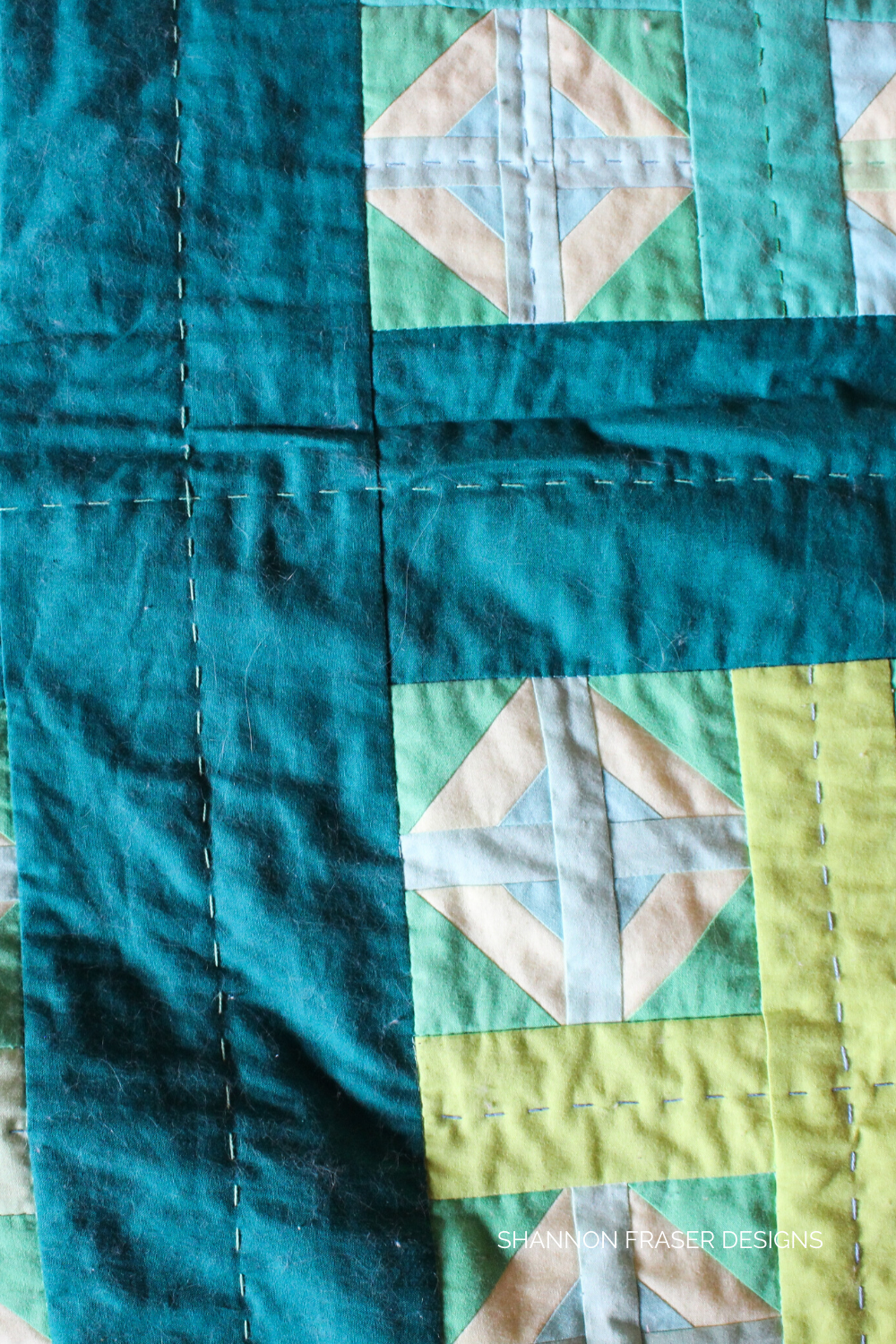 Up close shot of the Plus Infinity quilt after having the pet hair removed | How to safely remove pet hair from your quilts | Shannon Fraser Designs #crossquilt