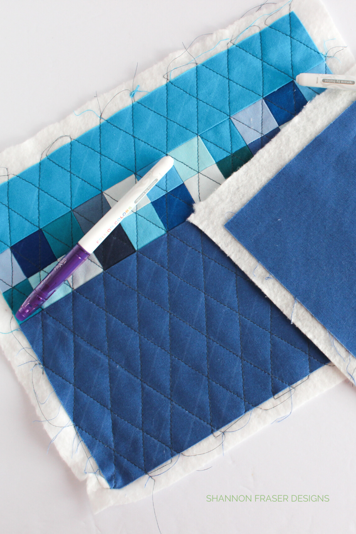 Blue patchwork mini quilt showing bleach stains from using Frixion markers