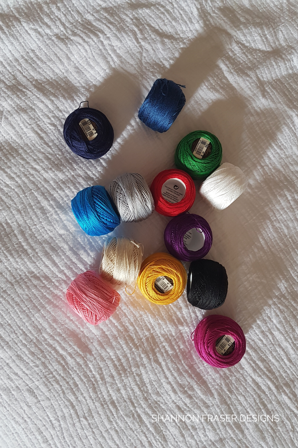 DMC Pearl cotton thread spools on a bed | Shopping Guide for Perle Cotton Thread | Shannon Fraser Designs #notions
