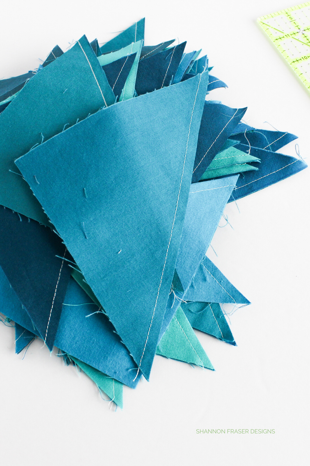 Stack of blue half square triangles ready to be pressed open and trimmed | Blue Odyssey quilt | Shannon Fraser Designs