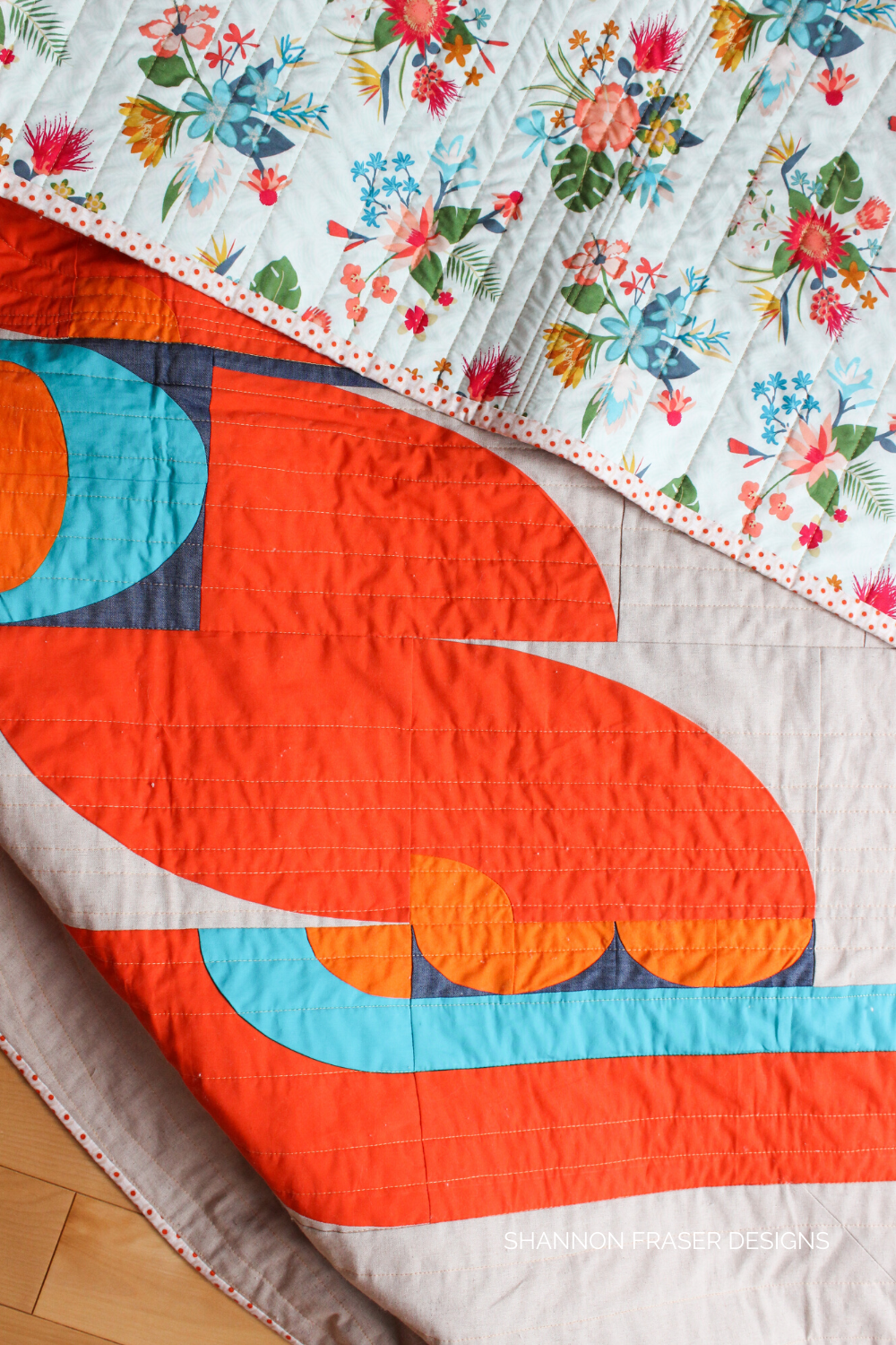 Lap Cloud Surfing quilt laid out on the floor with a peek at the floral backing showing