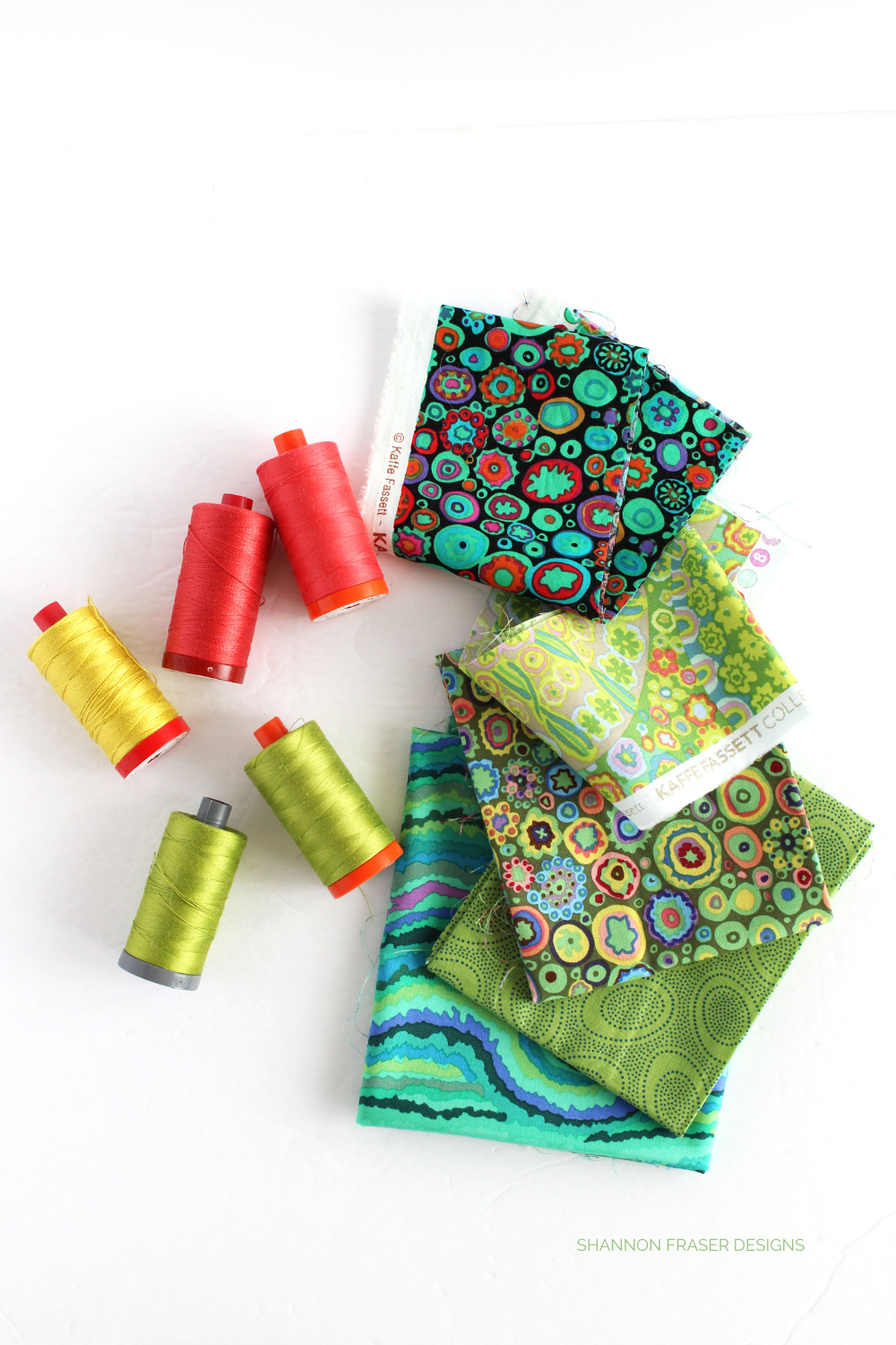 Kaffe Fassett fat quarters I received for the Aurifil Artisan April Challenge and the threads I paired with the modern needle turn appliqué wall hanging I quilted up #kaffefassett