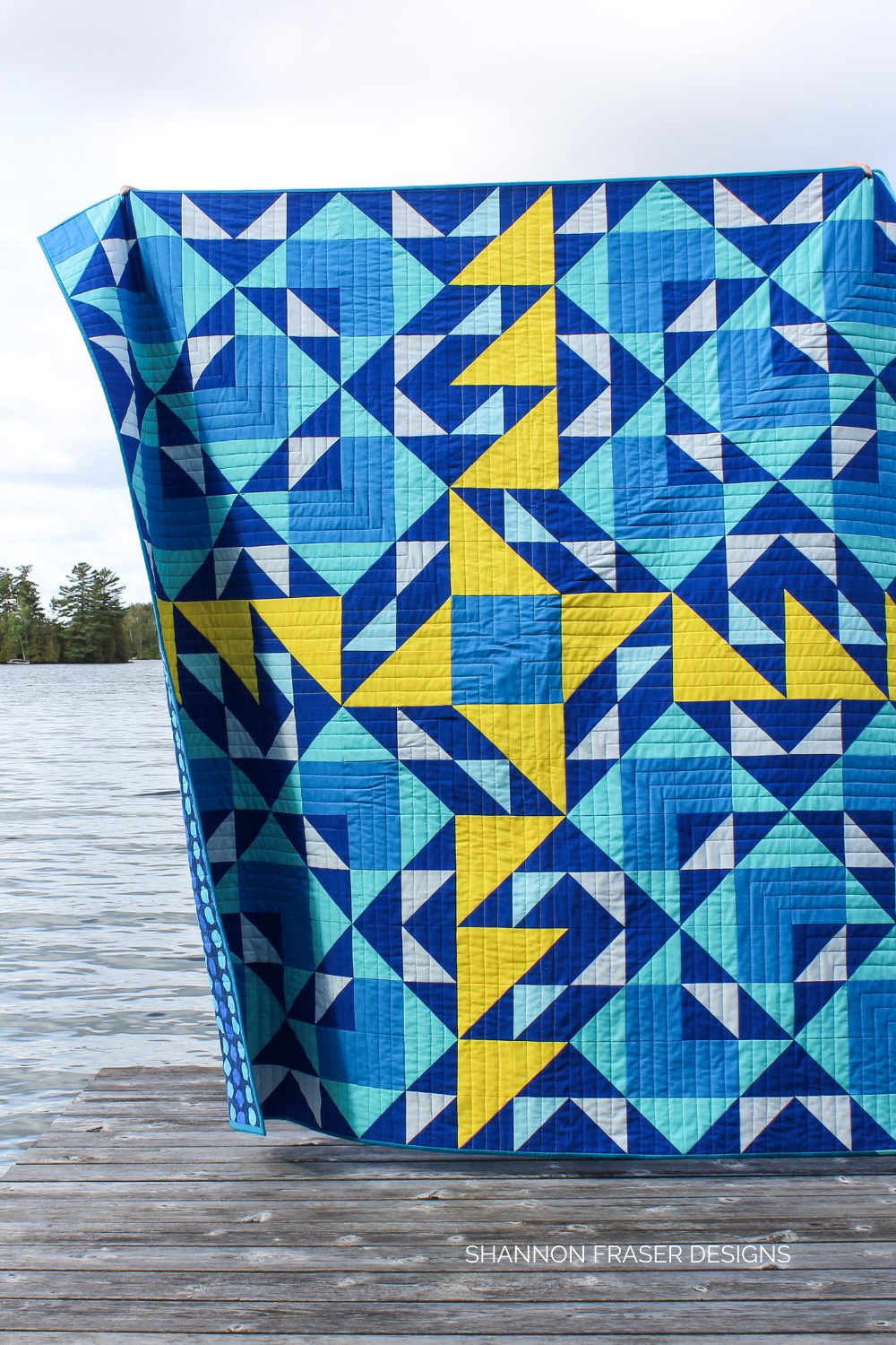 Blue and yellow Double Windmill Quilt on the dock in the summer | Featured in Curated Quilts Magazine | Shannon Fraser Designs #halfsquaretriangles
