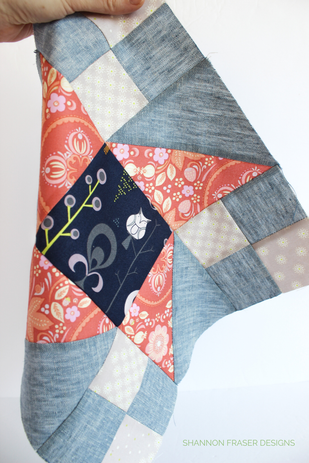 Close-up of the Irish Vortex quilt block in coral, cream, navy and chambray linen | Irish Vortex quilt pattern | Shannon Fraser Designs #quiltblock