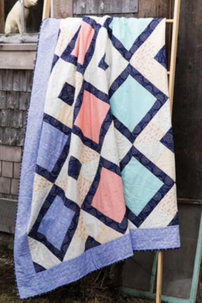 Festival Quilt hanging on a ladder against a barn with a dog in the window | Kaleidoscope Festival Quilt | Shannon Fraser Designs #quiltsinthewild